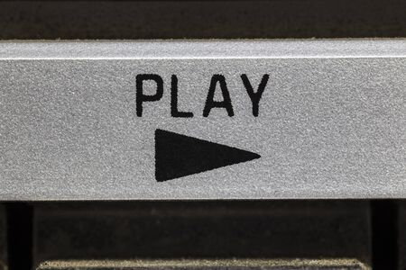 Macro close up photograph of play button on vintage boombox stereo.
