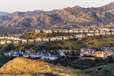 Rows of hilltop homes overlooking the San Fernando Valley in northern Los Angeles, California.  The Santa Susana Mountains are in the background.