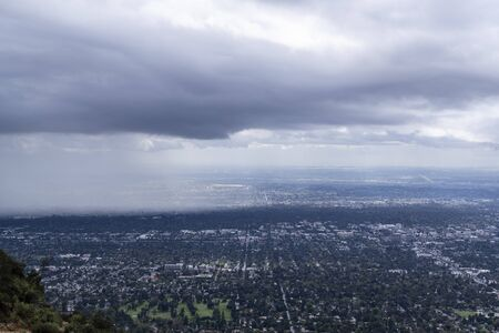 Mountaintop view of storm clouds and rain moving into Pasadena in Los Angeles County California.
