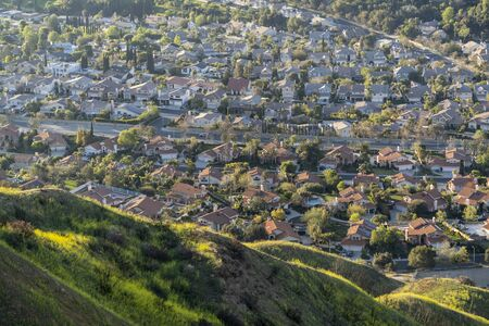 Suburban valley homes and green mountain hillsides in north Los Angeles, California.