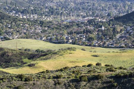 Suburban grasslands meadow with homes in background at Santa Monica Mountains National Recreation Area in Newbury Park, California.