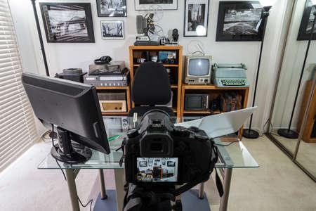 Home office vlogging studio with vintage electronics on shelves.