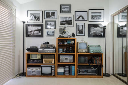 Bric-a-brac shelves wth collectable vintage electronics and framed black and white photos in small home office. Wall art is the photographers work.