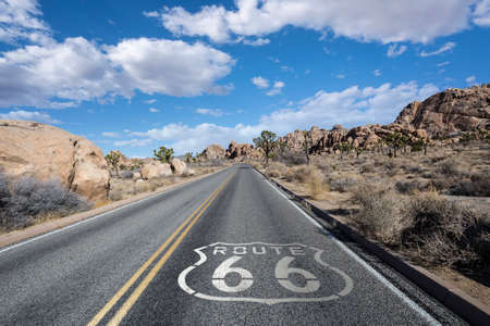California desert Joshua Tree highway with Route 66 pavement sign and clouds.