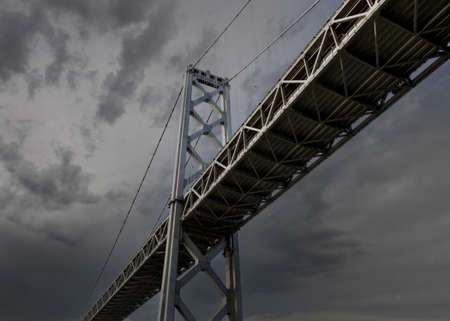 View below the San Francisco Oakland Bay Bridge with thunderstorm sky.