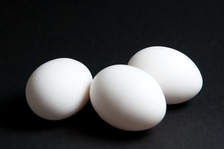 Three white eggs clustered on a black background