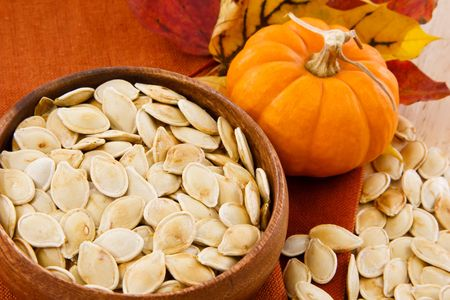 pumpkin seed: Toasted pumpkin seeds in a wooden bowl with scattered seeds and small pumpkin Stock Photo