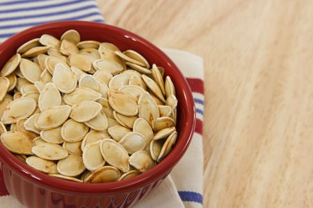 Healthy pumpkin seeds in a red bowl set against a red, white and blue towel make a healthy snack option photo