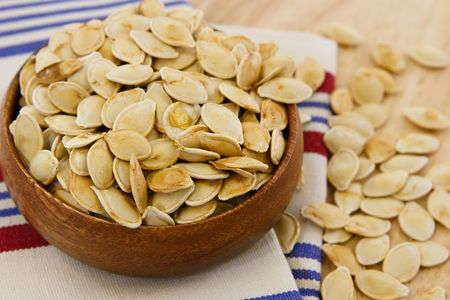 Toasted pumpkin seeds scattered against a table and striped towel with shallow depth of field photo