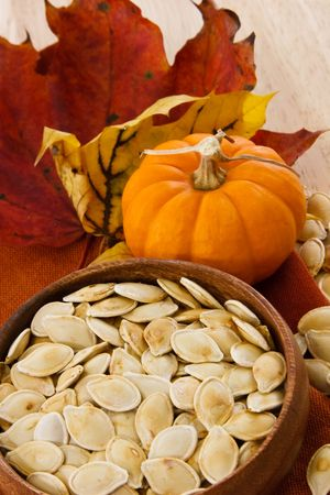 Wooden bowl with toasted pumpkin seeds, small pumpkin and autumn leaves.