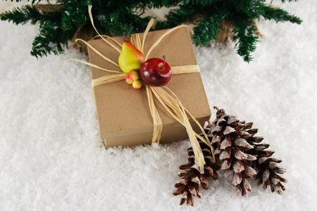 Celebrate the holidays with a nature-inspired gift in a brown kraft box accented with decorative fruit, set in a snowy background with glittery pinecones. photo
