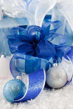Cool blue, white and silver wrapping paper and ribbon make a fresh and frosty holiday scene with presents nestled in snow, accented with ribbon and glittery ornaments. Stock Photo