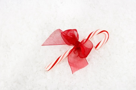 Red & White Candy Cane with Red Bow on Snowy Background Stock Photo - 8341500