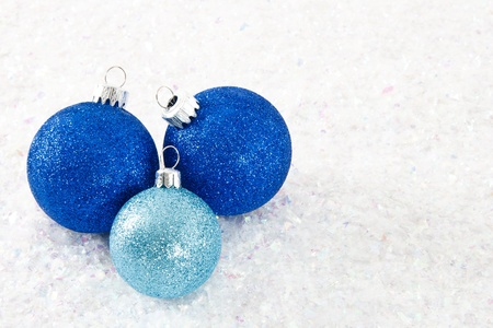 Sparkling glitter ornaments in shades of blue are clustered together on a frosty white snowy background Stock Photo