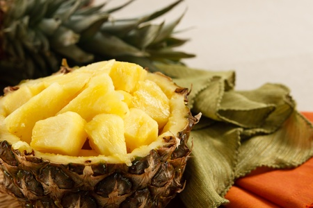 Fresh cut pineapple served in a natural bowl, set against colorful napkins on a linen tablecloth.