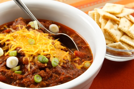 A hearty bowl of chili topped with shredded cheese and scallions makes a tasty lunch or dinner Banco de Imagens