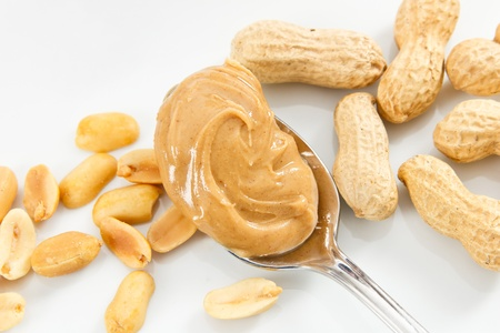 allergic ingredients: Creamy peanut butter and peanuts against a white tray show healthy foods that are also allergens