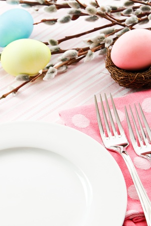 pink pussy: A festive pastel pink table setting is decorated for Easter with traditional dyed eggs and pussy willows leaving ample copy space on a white plate