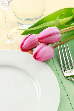 Three pink tulips grace a table setting in fresh Spring colors making a perfect background for Easter or Mothers Day promotions - ample copy space provided with the empty white plate Фото со стока
