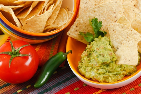 Close up of fresh Guacamole with corn chips, accented with tomato, & jalapeno pepper on a colorful background.