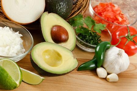 avocado: Avocado fresco circondato da cipolla, pomodoro, aglio, peperoni del jalapeno e calce, pronto per la preparazione di guacamole