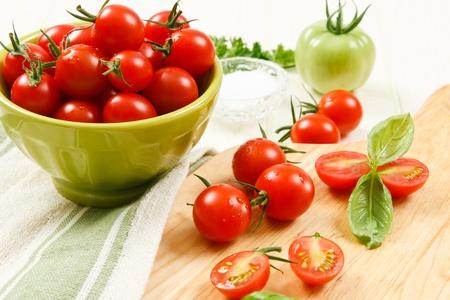 tomate cherry: Bol de tomates cherry rojos maduros con tomates en rodajas y todo en un tablero de corte acentuado con albahaca.