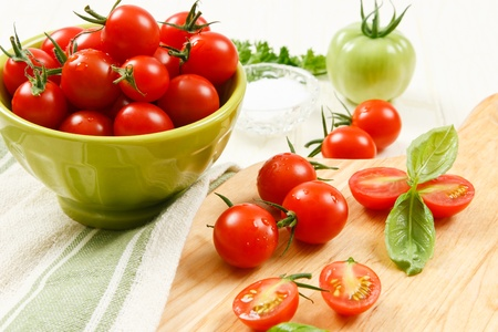 Bowl of ripe red cherry tomatoes with sliced and whole tomatoes on a cutting board accented with basil.