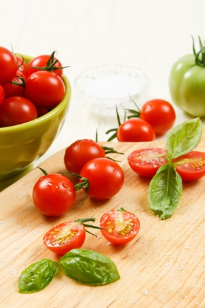 Ripe red cherry tomatoes on a cutting board sprinkled with kosher salt Stock Photo - 10361592