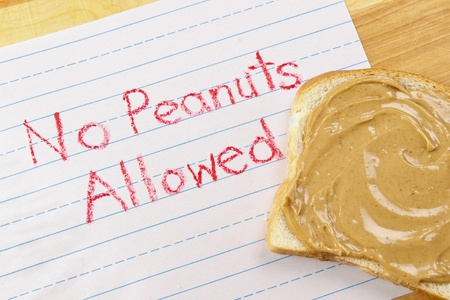 allergens: Lined primary school paper with No Peanuts Allowed written in red crayon warns against peanut products which are dangerous food allergens Stock Photo