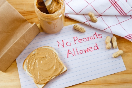 food allergy: Overhead view of peanut butter on bread with red crayon warning against peanuts which are a dangerous allergen for many children and adults.