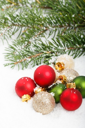 Colorful red and green Christmas ornaments in the snow with pine boughs in the background Stock Photo - 11718608