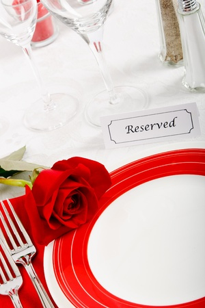A romantic red and white place setting shows a reserved table at an elegant restaurant ready to celebrate an anniversary or Valentine's Day. Archivio Fotografico