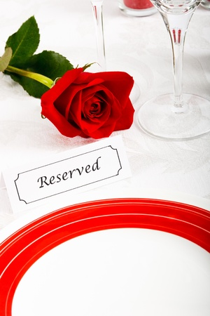 A romantic red and white place setting shows a reserved table at an elegant restaurant ready to celebrate an anniversary or Valentine's Day. Stock Photo - 12077530