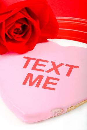 A pink cookie and red rose use the tech-oriented phrase Text Me to send a flirtatious message to a loved one. Stock Photo - 12077529