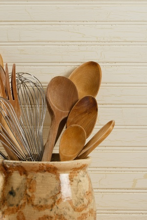old items: Wooden spoons and wire whisks in an old yellow and brown pot against a weathered wood background. Stock Photo