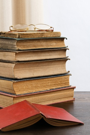A stack of aged antique books with eyeglasses on top and an open red hardcover book in the foreground. photo