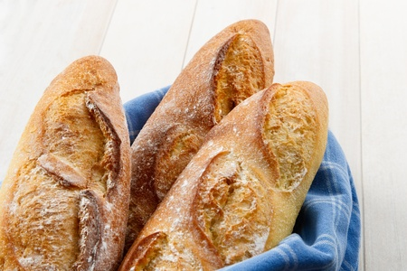 french bread boule: Overhead view of three fresh baked crusty French Baguettes dusted with flour and wrapped in a blue towel