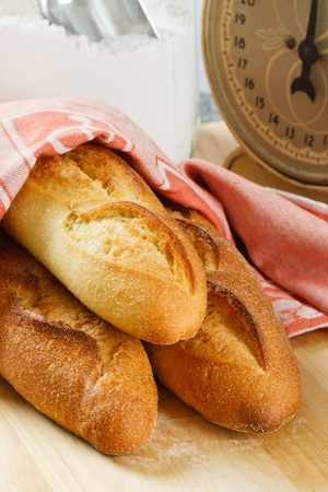 Three loaves of fresh baked baguette bread with flour and scale in the background Фото со стока