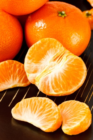 mandarin oranges: Close up overhead view of fresh, healthy whole and peeled mandarin oranges against a black background Stock Photo