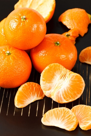 mandarin oranges: Overhead view of fresh, healthy whole and peeled mandarin oranges against a black background Stock Photo