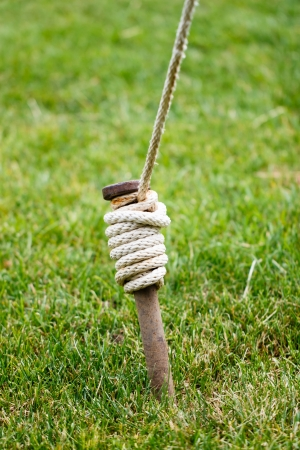 A rusty tent stake wrapped and tied with white rope is securely anchored in a green grass lawn