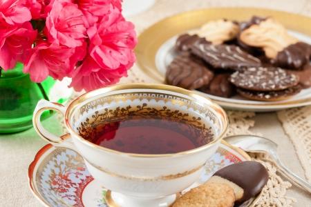 レースのテーブル クロスのクッキーと明るいピンクのツツジがアクセントにヴィンテージの茶碗で熱いお茶