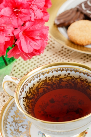 tea time: Overhead view of hot tea in a vintage teacup accented with azaleas and a plate of cookies in the background Stock Photo