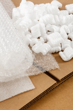 material: Protective packaging materials atop brown corrugate boxes show an assortment of shipping supplies Stock Photo