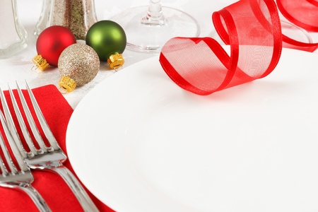 Holiday ornaments decorate a restaurant table setting in festive red and green Christmas colors with copy space on an empty white plate