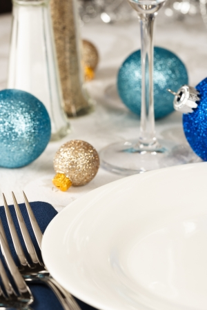 Christmas ornaments in blues and gold decorate a festive holiday table with an empty white plate providing copy space Stock Photo - 14946912