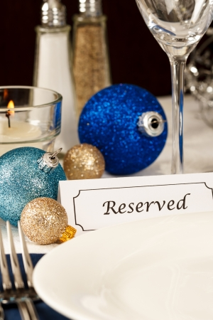 A holiday table setting with an empty plate providing copy space is decorated with blue and gold ornaments and a placard showing a reserved place Stock Photo - 14946917
