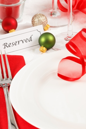 A festive red and green Christmas table setting is adorned with ribbon and ornaments leaving copy space on a white plate photo