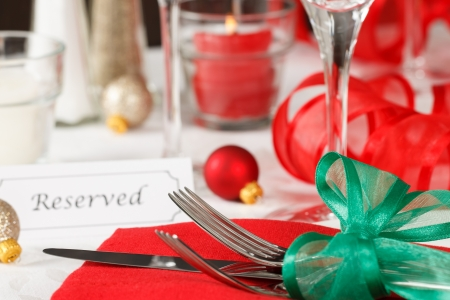 Close up view of a holiday table setting with red and green decorations and placard showing a reserved space photo