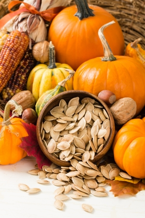 Pumpkins, gourds, nuts and Indian corn, also known as flint corn, surround a wooden bowl overflowing with healthy toasted pumpkin seeds